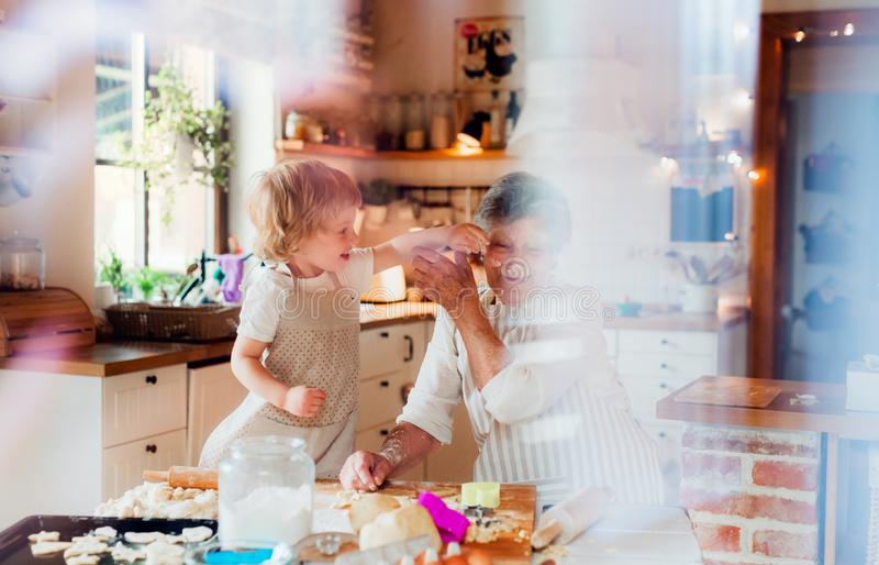 Senior grandmother with small toddler boy making cakes at home. royalty free stock photos