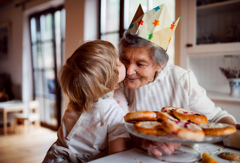 Senior grandmother with small toddler boy making cakes at home, kissing. stock image