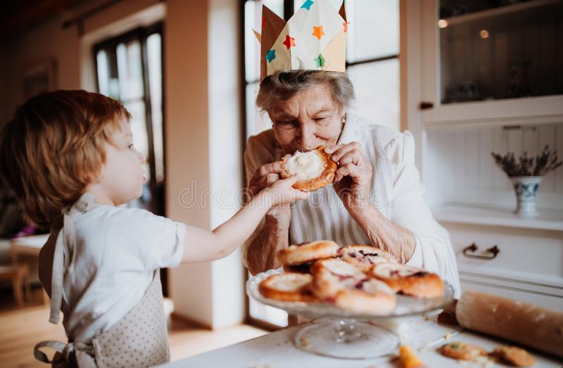 Senior grandmother with small toddler boy making and eating cakes at home. Happy senior great grandmother with small toddler boy making and eating cakes at home royalty free stock photos