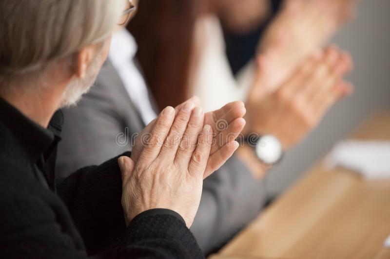 Senior gray-haired businessman clapping hands attending conferen royalty free stock images