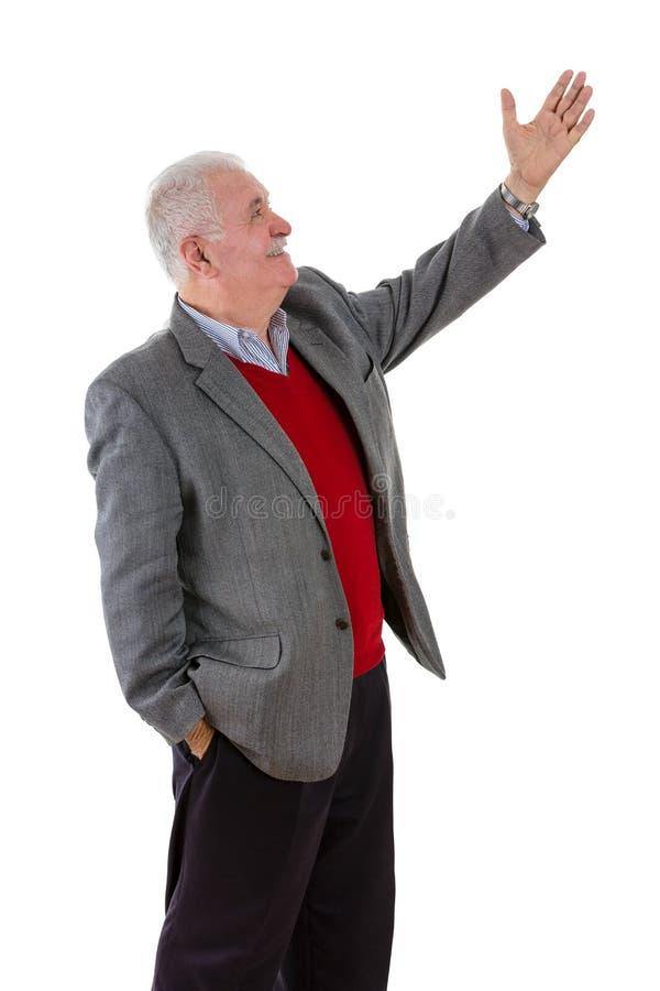 Senior grey-haired man raising his left arm royalty free stock image