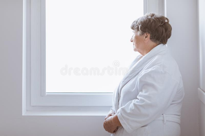 Senior grey lady wearing white bathrobe standing by the window at nursing home. Senior grey lady wearing white bathrobe standing by the window at home royalty free stock images