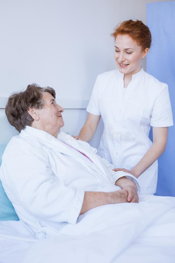 Senior woman lying in white hospital bed with young helpful nurse holding her hand royalty free stock photo