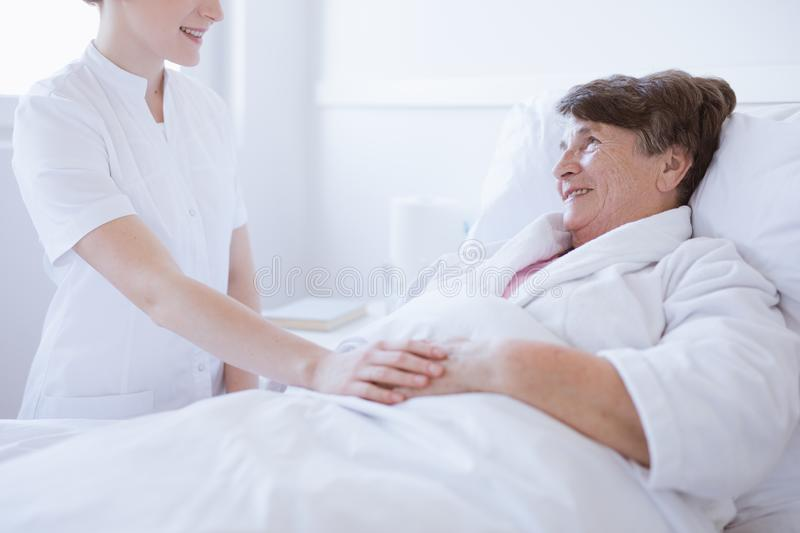 Senior woman lying in white hospital bed with young helpful nurse holding her hand royalty free stock photos