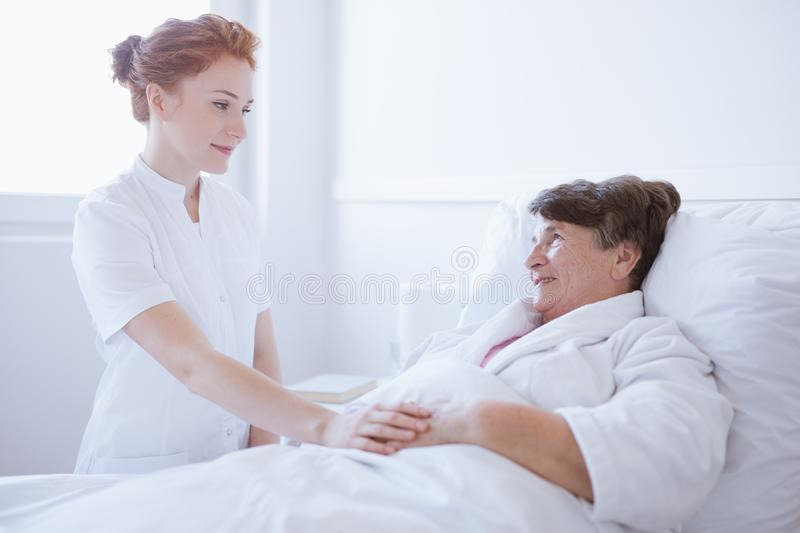 Senior grey woman lying in white hospital bed with young helpful nurse holding her hand stock photography