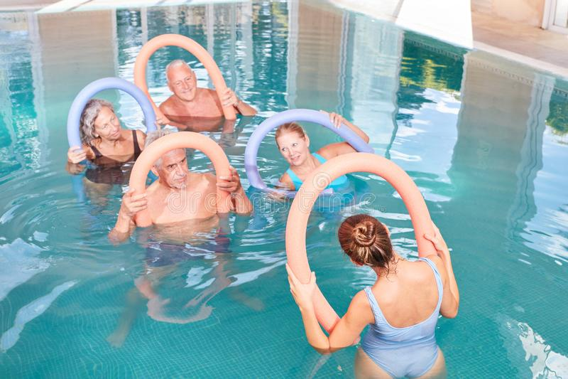 Senior group does water aerobics. Senior group is doing healthy water gymnastics as rehab in swimming pool royalty free stock photography