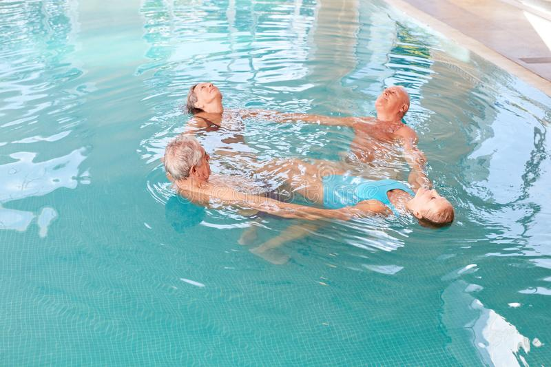Senior group does water aerobics. Senior group is doing water aerobics in a rehab course royalty free stock photo