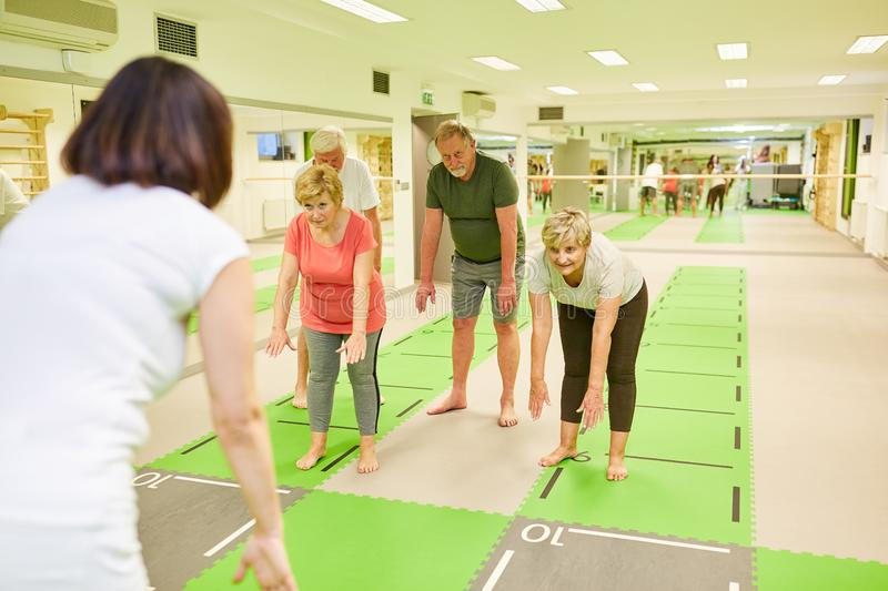 Senior group makes healthy back training. In rehab under the guidance of trainer stock photo