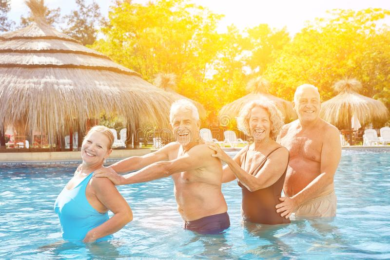 Senior group makes polonaise in the hotel pool royalty free stock images