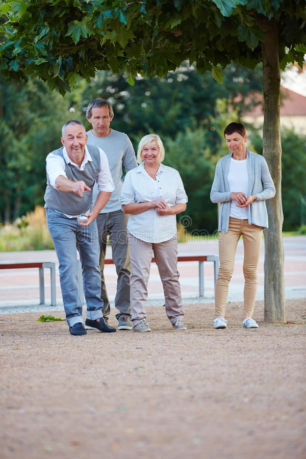 Senior group playing boule in summer stock images