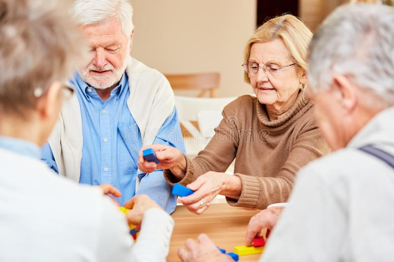 Senior group plays with colorful building blocks royalty free stock photo