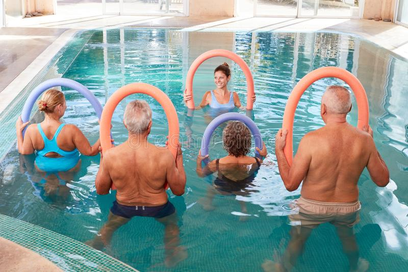 Back gymnastics course in rehab. Senior group in the swimming pool in a back exercises course in rehab royalty free stock image