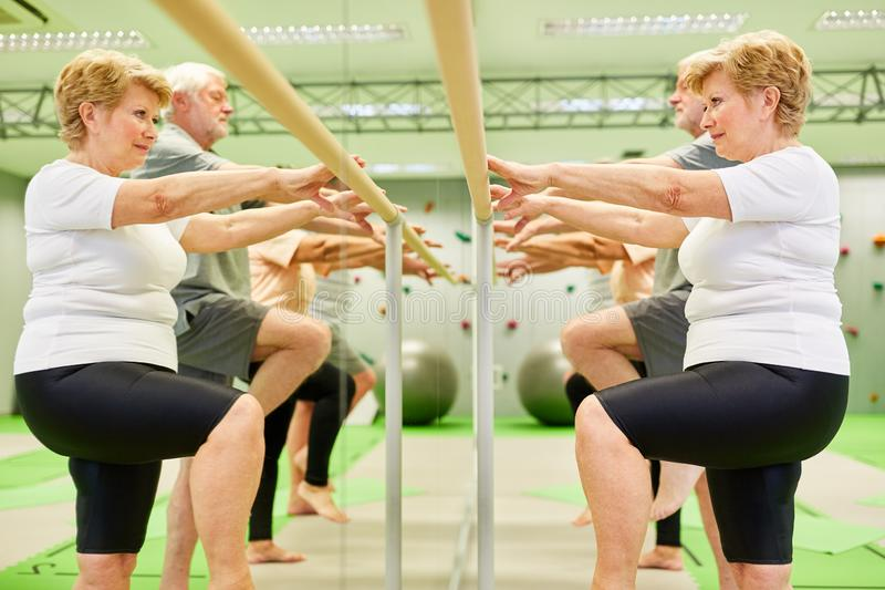 Senior group trains motor skills and coordination. At the ballet bar in physiotherapy stock images