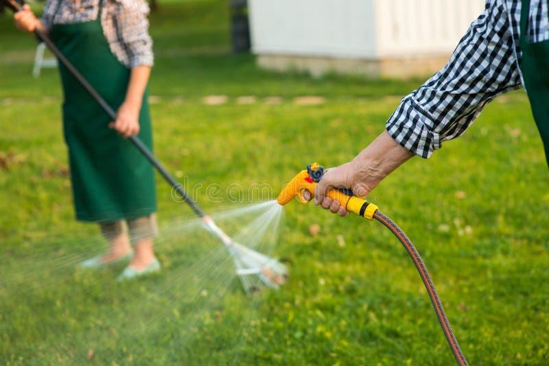 Senior hand holding water hose. stock photo