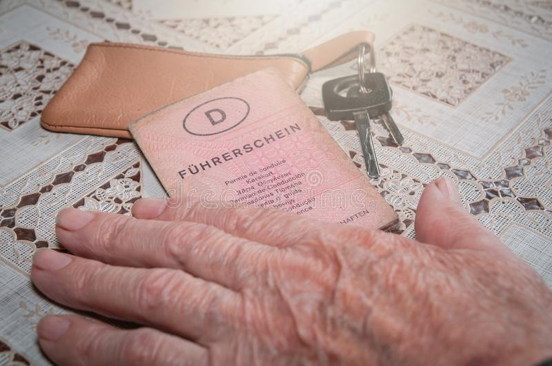 Senior hand with old German driving license `Führerschein` and car key. Old senior hand holding German driving license `Führerschein`. Car keys laying on royalty free stock photo