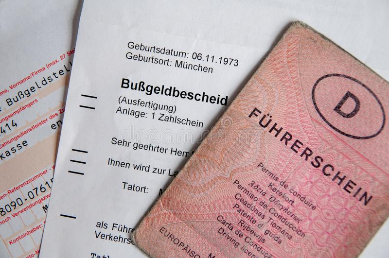Senior hand with old German driving license and driving fine. Old senior hand holding German driving license and driving fine stock photography