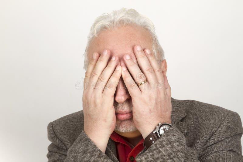 Senior hands his face stock photos