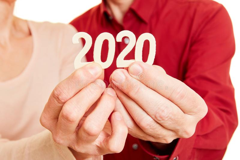 Senior hands show year 2020 as a number royalty free stock photo