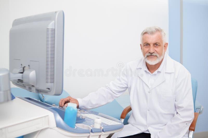 Senior man sitting at ultrasound apparatus at hospital. royalty free stock photography