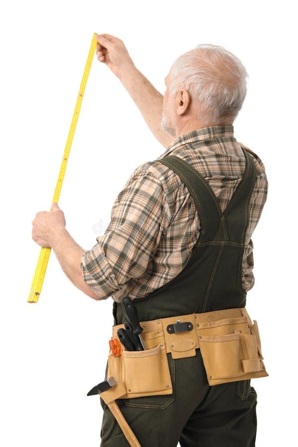 Senior handyman measuring