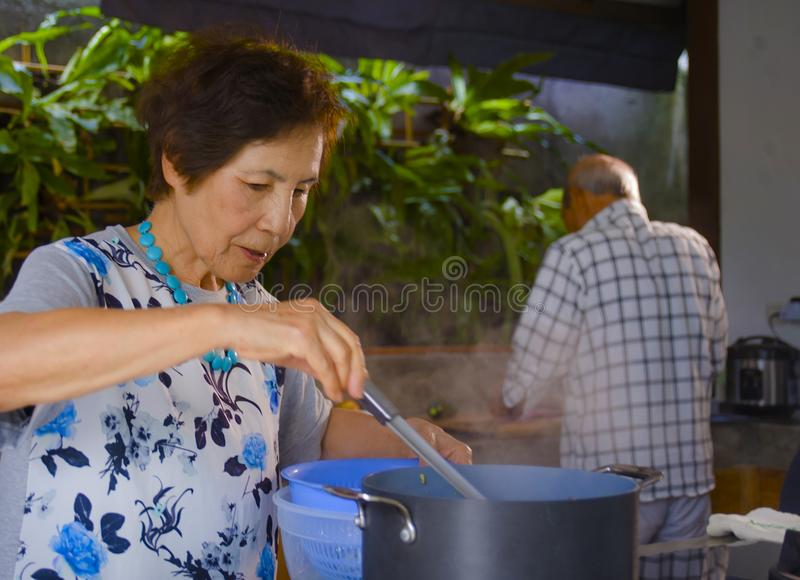 senior happy and beautiful retired Asian Japanese couple cooking together at home kitchen enjoying preparing meal relaxed royalty free stock images