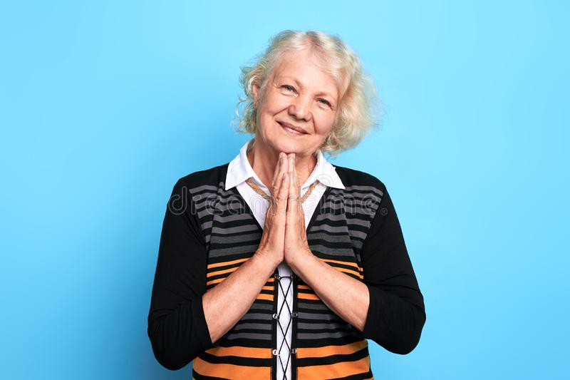 Senior happy blonde woman pressing palms together, praying the God royalty free stock images