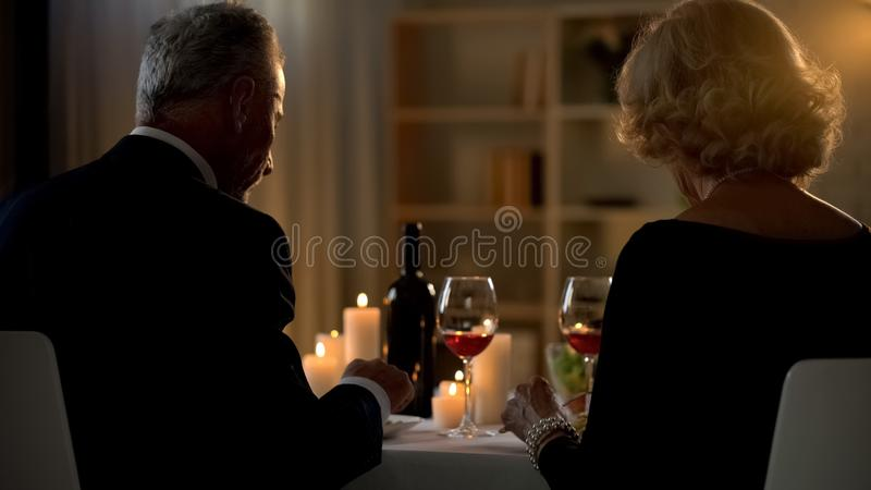 Senior happy couple eating dinner in restaurant back view, anniversary date royalty free stock photography