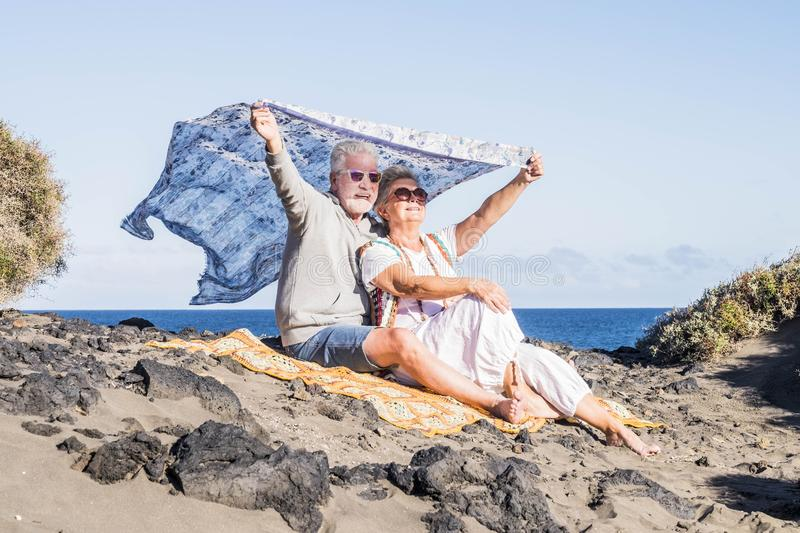 Senior happy couple enjoy leisure outdoor together at the beach with. ocean in background. hippy style casual clothes and travel royalty free stock photo
