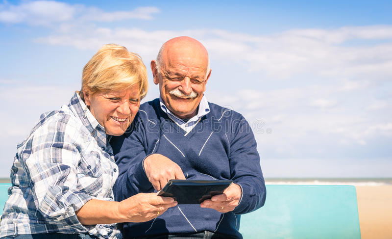 Senior happy couple having fun with a tablet at the beach stock images