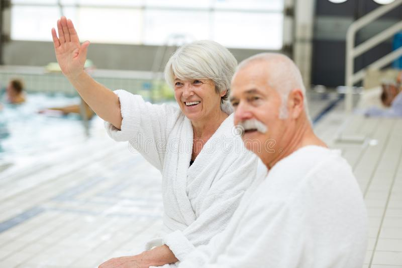 Senior happy couple in swimming pool royalty free stock images