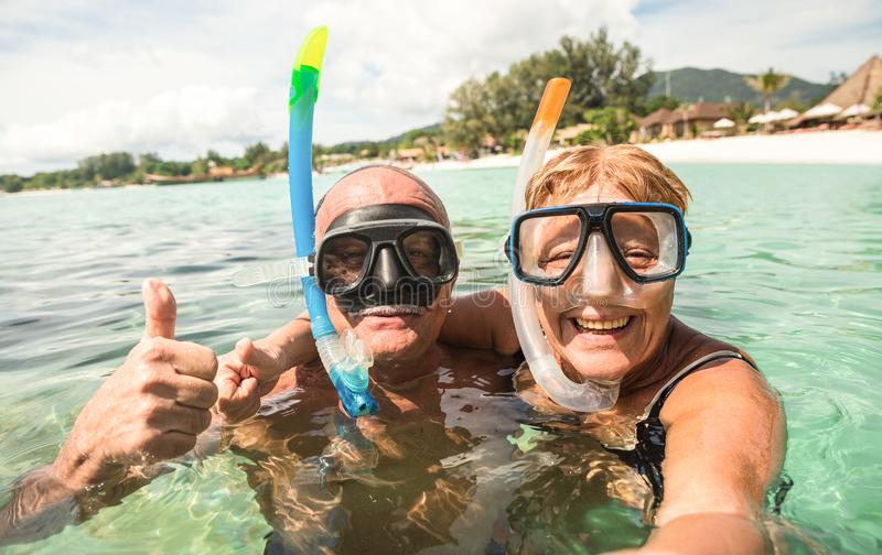 Senior happy couple taking selfie with scuba snorkeling masks stock photo