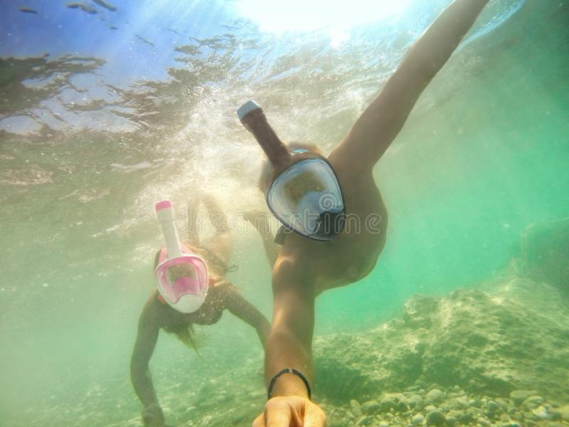 Senior happy couple taking selfie in tropical sea excursion with water camera - Boat trip snorkeling in exotic scenarios - Active stock image