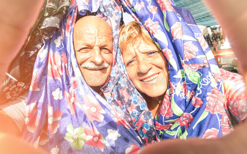Senior happy couple taking a selfie at the week clothes market stock image