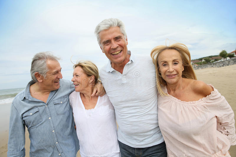 Senior happy people walking on sandy beach stock image