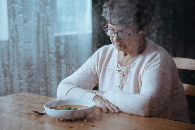 Senior having lack of appetite. Sad, senior woman having lack of appetite stock photo