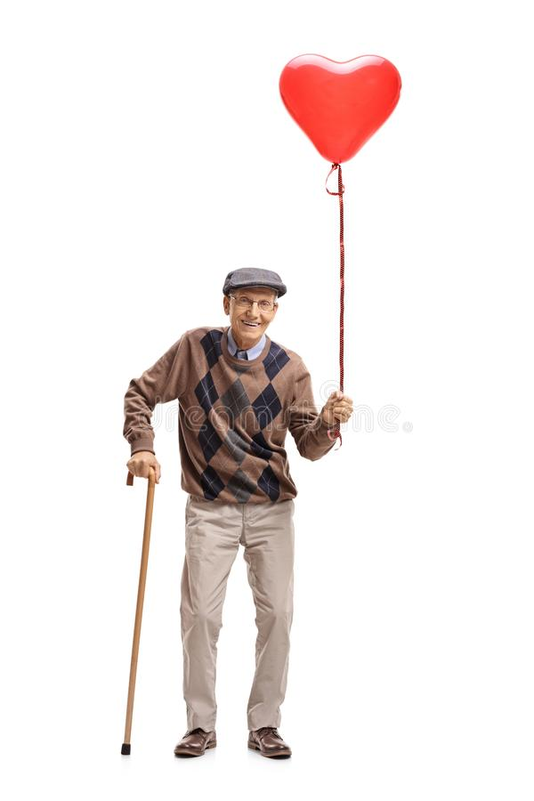 Senior with a heart shaped balloon and a cane royalty free stock photo