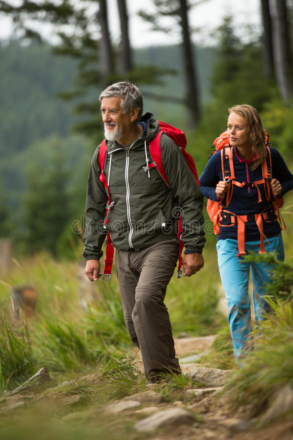 Senior hiking in high mountains with his daughter. Active senior hiking in high mountains with his daughter stock image