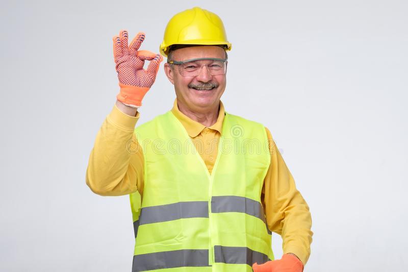 Senior hispanic construction worker in hard hat showing ok sign stock photos