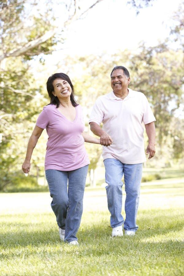Senior Hispanic Couple Running In Park stock images