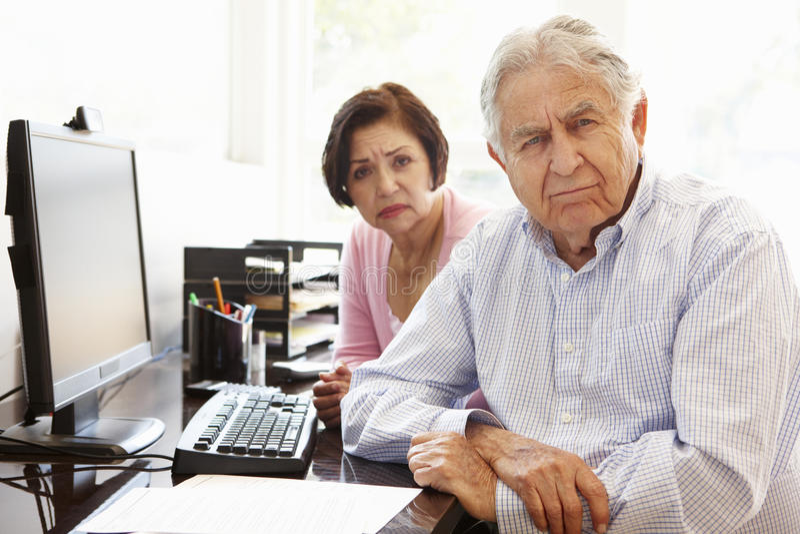 Senior Hispanic couple working on computer at home stock photo