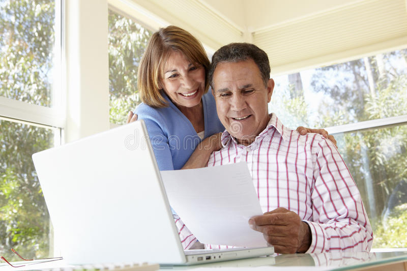 Senior Hispanic Couple Working In Home Office royalty free stock images