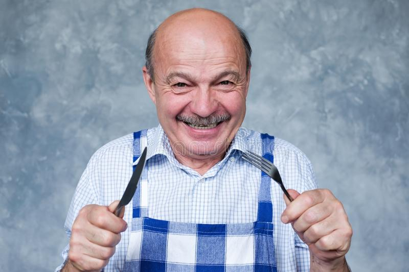 Senior hispanic hungry man holding a fork and a knife. royalty free stock photos