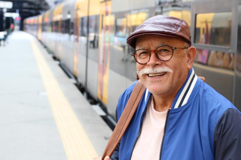Senior Hispanic man am Bahnhof stockbild