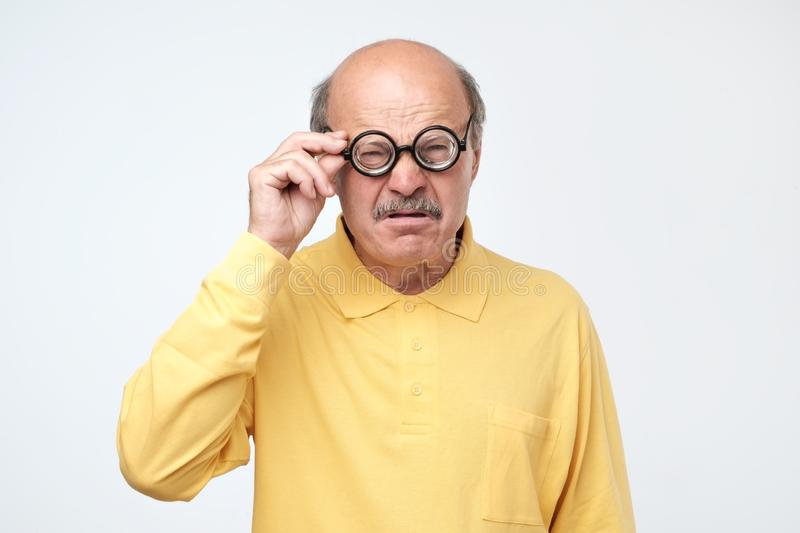 Senior hispanic man looking at camera wearing funny glasses. Funny senior hispanic man looking at camera wearing funny glasses. Negative facial emotion stock photo