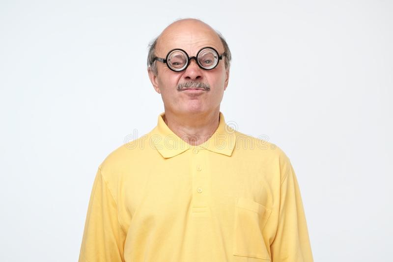 Senior hispanic man looking at camera wearing funny glasses. Funny senior hispanic man looking at camera wearing funny glasses. Negative facial emotion stock images