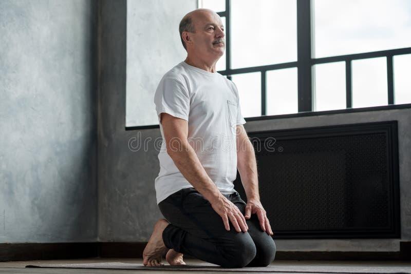 Senior hispanic man practicing yoga at home in vajrasana pose. Restorative position after practice stock image