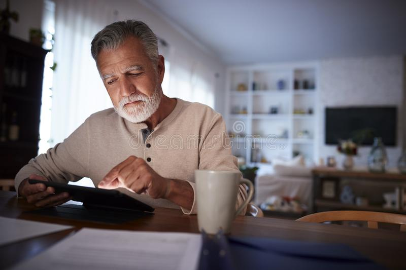 Senior Hispanic man sitting at his dining table reading an e book at home in the evening, close up stock image