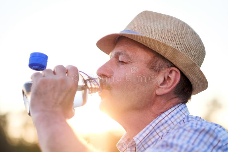 Senior hispanic man in summer hatdrinking fresh water. Thirsty senior hispanic man in summer hatdrinking fresh water close up outdoor at park royalty free stock photography