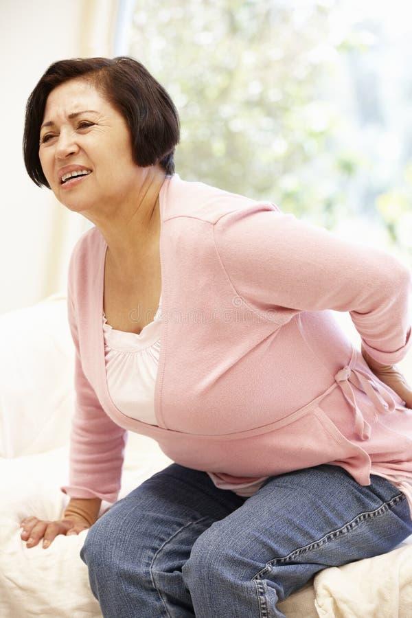 Senior Hispanic woman with backache stock photo