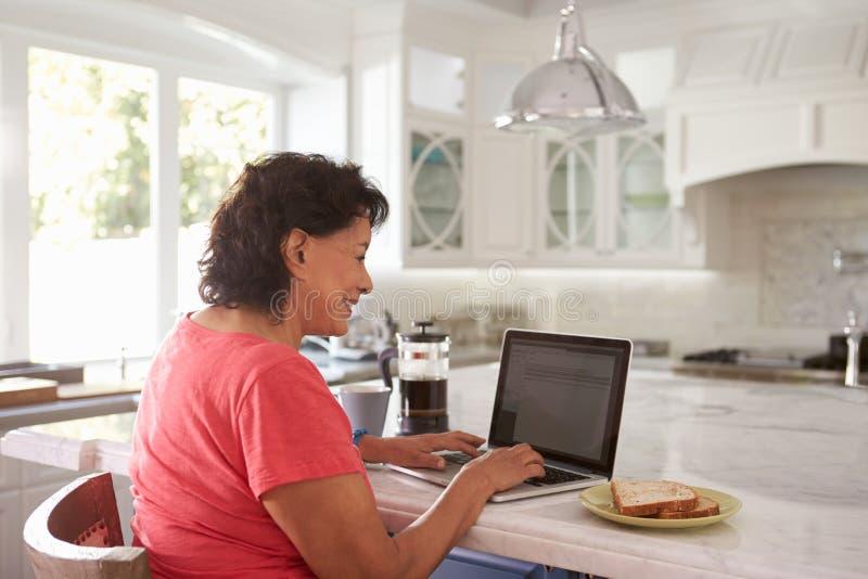 Senior Hispanic Woman Sitting At Home Using Laptop stock images